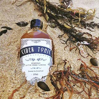 Bottle of Cider Tonic's apple cider vinegar on the beach
